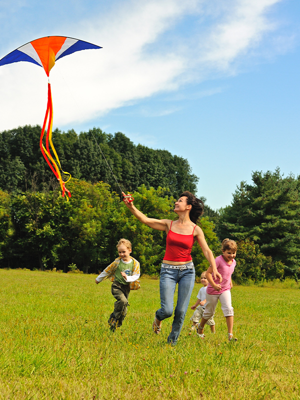 Mom with two kids flying a kite in a field. Blue skies above.